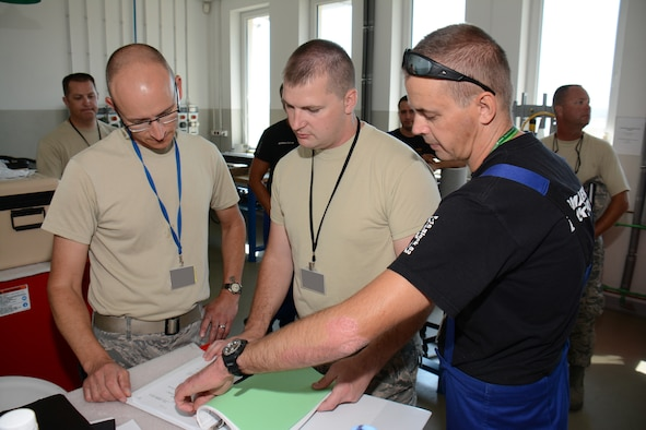 U.S. Air Force Senior Master Sgt. Peter Seibel, left, armament section supervisor, joins U.S. Air Force Tech. Sgt. Steven Heggie, center, aircraft armament specialist for the Wisconsin Air National Guard's 115th Fighter Wing to review technical order data with their Polish air force counterparts from the 10th Fighter Squadron at Łask Air Base Sept. 1, 2015, while deployed in support of U.S. Aviation Detachment Rotation 15-4. The annual training exercise hosted by the Av-Det is designed to enhance bilateral defense ties between Poland and the United States, while strengthening the interoperability of NATO Allies. (U.S. Air National Guard Photo by Master Sgt. Paul Gorman/Released)