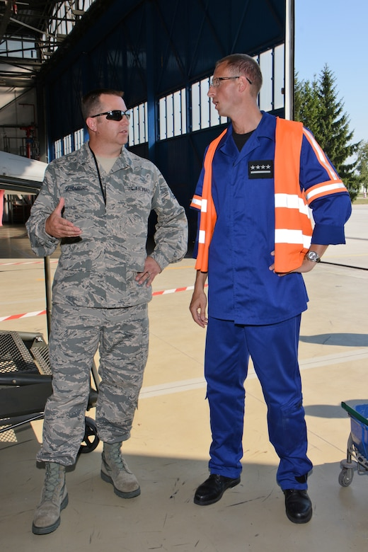 U.S. Air Force Master Sgt. John Schomburg, left, aircraft armament specialist for the Wisconsin Air National Guard's 115th Fighter Wing compares aircraft maintenance procedures with a Polish maintenance officer from the 10th Fighter Squadron at Łask Air Base Sept. 1, 2015, while deployed in support of U.S. Aviation Detachment Rotation 15-4. The annual training exercise hosted by the Av-Det is designed to enhance bilateral defense ties between Poland and the United States, while strengthening the interoperability of NATO Allies. (U.S. Air National Guard Photo by Master Sgt. Paul Gorman/Released)
