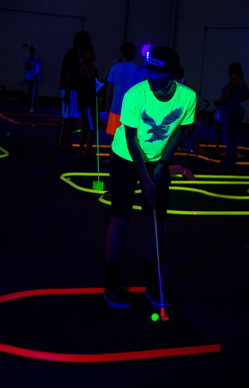 Carson, son of U.S. Air Force Col. Joseph Locke, 93d Air Ground Operations Wing commander, swings a club during Recharge for Resiliency Glow in the Dark miniature golf, July 24, 2015, at Moody Air Force Base, Ga. Recharge for Resiliency was designed to assist families, couples and single Airmen in reintegrating and recharging before and after a deployment. (U.S. Air Force photo by Senior Airman Ceaira Tinsley/Released)