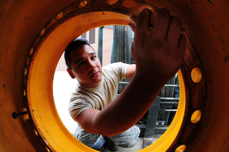 Airman 1st Class Chaiya Thamvongsa, 509th Civil Engineer Squadron pavement and equipment journeyman, inspects a loader's tire at Whiteman Air Force Base, Mo., Oct. 5, 2015. If the pavement and equipment shop discover any defects, such as holes or cracks, on the tires, they will turn them over to vehicle maintenance for repair. (U.S. Air Force photo by Senior Airman Keenan Berry/Released)