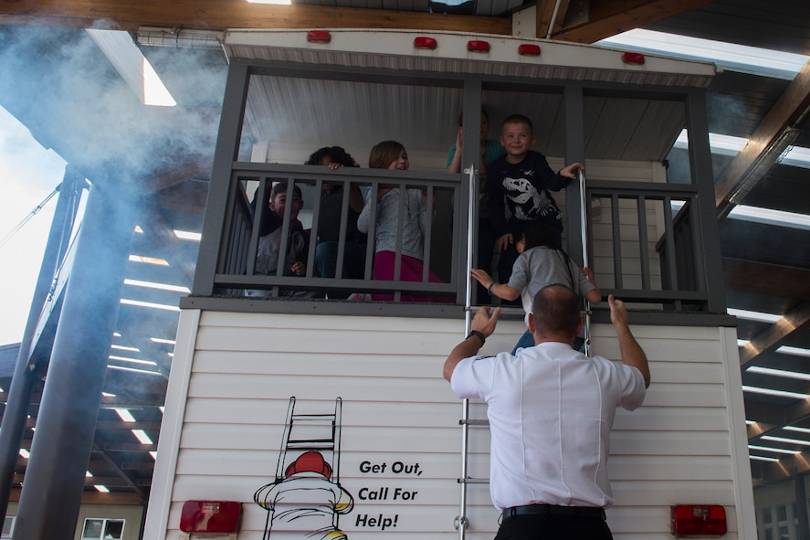 Ingo Alf, a 52nd Civil Engineer Squadron fire inspector, helps Bitburg Elementary School students down a ladder while practicing exiting a building during a visit from the Spangdahlem Fire Department at BES on Bitburg Annex, Germany, Oct. 8, 2015. The pretend house fire taught the students to check if doors are warm with the back of their hands and to call for help once you are out of the house. (U.S. Air Force photo by Airman 1st Class Luke J. Kitterman/Released)