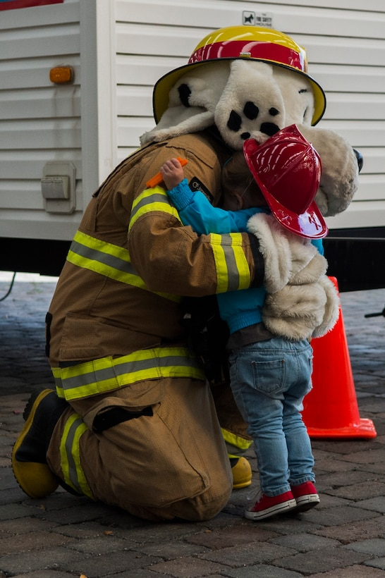 """Sparky, the 52nd Civil Engineer Squadron firefighters' mascot, hugs a child during a visit from the CES firefighters at Bitburg Elementary School on Bitburg Annex, Germany, Oct. 8, 2015. The firefighters demonstrated the importance of fire-safety to the students in observance of Fire Prevention Week. """"Hear the beep where you sleep, every bedroom needs a working smoke alarm"""" is this year's theme for Fire Prevention Week. (U.S. Air Force photo by Airman 1st Class Luke J. Kitterman/Released)"""