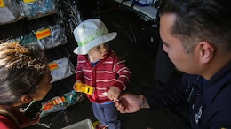 A member of the San Francisco Fire Department gives a sticker to a young young boy during a humanitarian assistance and disaster relief static display at Marina Green Park, San Francisco, Oct. 9, 2015, as part of San Francisco Fleet Week 2015. SFFW 15' is a week-long event that blends a unique training and education program, bringing together key civilian emergency responders and Naval crisis-response forces to exchange best practices focused on humanitarian assistance disaster relief with particular emphasis on defense support to civil authorities.