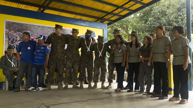 U.S. Marines and the teachers and staff of Concepcion Elementary School sing together during an intermission at the ribbon cutting ceremony Oct. 8, during Amphibious Landing Exercise 2015 in Puerta Princesa, Philippines. PHIBLEX is an annual, bilateral training exercise conducted by members of the Armed Forces of the Philippines alongside U.S. Marine and Navy Forces. It focuses on strengthening the partnership and relationships between the two nations across a range of military operations, including disaster relief and complex expeditionary operations. The ribbon cutting ceremony signified the end of the Humanitarian Civic Assistance projects at the Concepcion and Binduyan Elementary schools. (U.S. Marine photo by Cpl. Robert Williams Jr./Released)