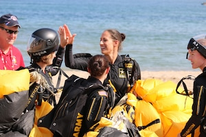 The U.S. Armed Forces Parachuting Team featuring the Army Golden Knights Parachuting Team pass around high-fives after a great round during the formation sky diving event.  The U.S. women won gold while setting the CISM World Record in Formation Sky Diving.