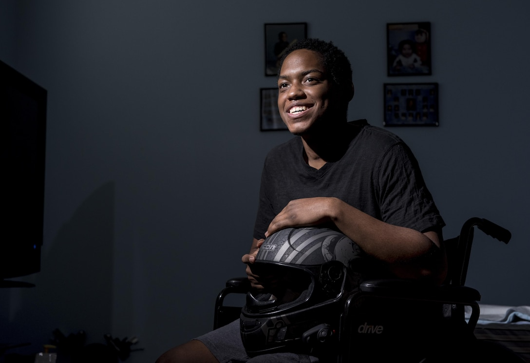 Spc. Nicolas Laboy, U.S. Army Reserve information technology specialist for the 416th Theater Engineer Command, poses in his wheelchair at his house in Bolingbrook, Ill., Sept. 29, holding his motorcycle helmet that saved his life during an accident three months earlier. Laboy is expected to walk again after three more months of physical therapy. During his accident, Laboy broke his right leg, received a third-degree burn in his left thigh, severed his kidney and liver, fractured his lower spine and his right shoulder, and suffered internal bleeding in his brain. (U.S. Army photo by Master Sgt. Michel Sauret)