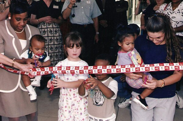 Five-year-old Amanda Shaw (center) helps cut the ribbon at the grand opening of the Defense Logistics Agency's Child Development Center in August 1998. Amanda, the daughter of DLA Finance employee Joe Shaw, and her younger sister Megan were some of the first enrollees at the center.