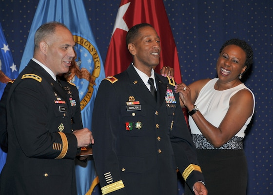 Army Brig. Gen. Charles R. Hamilton, center, gets promoted by Army Deputy Chief of Staff for Logistics Lt. Gen. Gustave F. Perna, and Hamilton's wife Regina during a promotion ceremony July 10 at Fort Belvoir, Virginia. Hamilton was promoted days before he took command of DLA Troop Support at a change of command ceremony July 13.