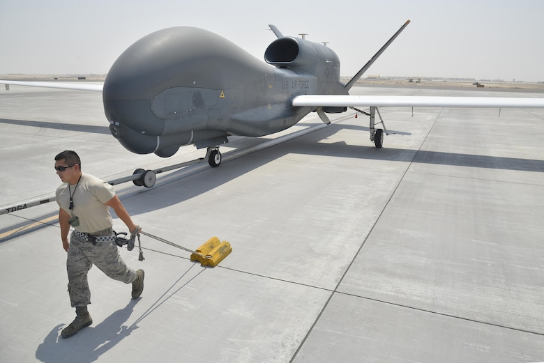 Senior Airman Jose pulls a set of chalks while escorting an RQ-4 Global Hawk back to a hangar during ground operations at an undisclosed location in Southwest Asia September 18, 2015. Jose is an assistant dedicated crew chief assigned to the 380th Expeditionary Aircraft Maintenance Squadron. (U.S. Air Force photo/Tech. Sgt. Christopher Boitz)