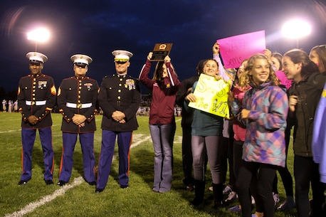 Maj. Christopher L. Buck, Recruiting Station Lansing commanding officer, third from left, presents Lisa Semerly, Okemos High School coach, with the Recruiting Station Lansing High School Coach of the Year Award on the Okemos football field, Oct. 9, 2015. Each year, RS Lansing solicits nominations from high schools throughout Michigan and recognizes one male and one female coach that exemplifies the Marine Corps values of honor, courage and commitment.