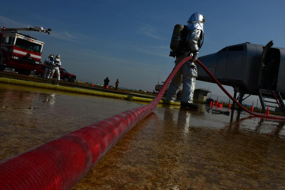 An 8th Civil Engineer Squadron Airman holds the water hose while fellow firefighters extinguish an aircraft fire during Beverly Pack 16-1 at Kunsan Air Base, Republic of Korea, Oct. 07, 2015. The aircraft fire is one of the many exercises that the firefighters participate in as a refresher training to sharpen their skills in the case of a real world emergency. (U.S. Air Force photo by Senior Airman Ashley L. Gardner/Released)