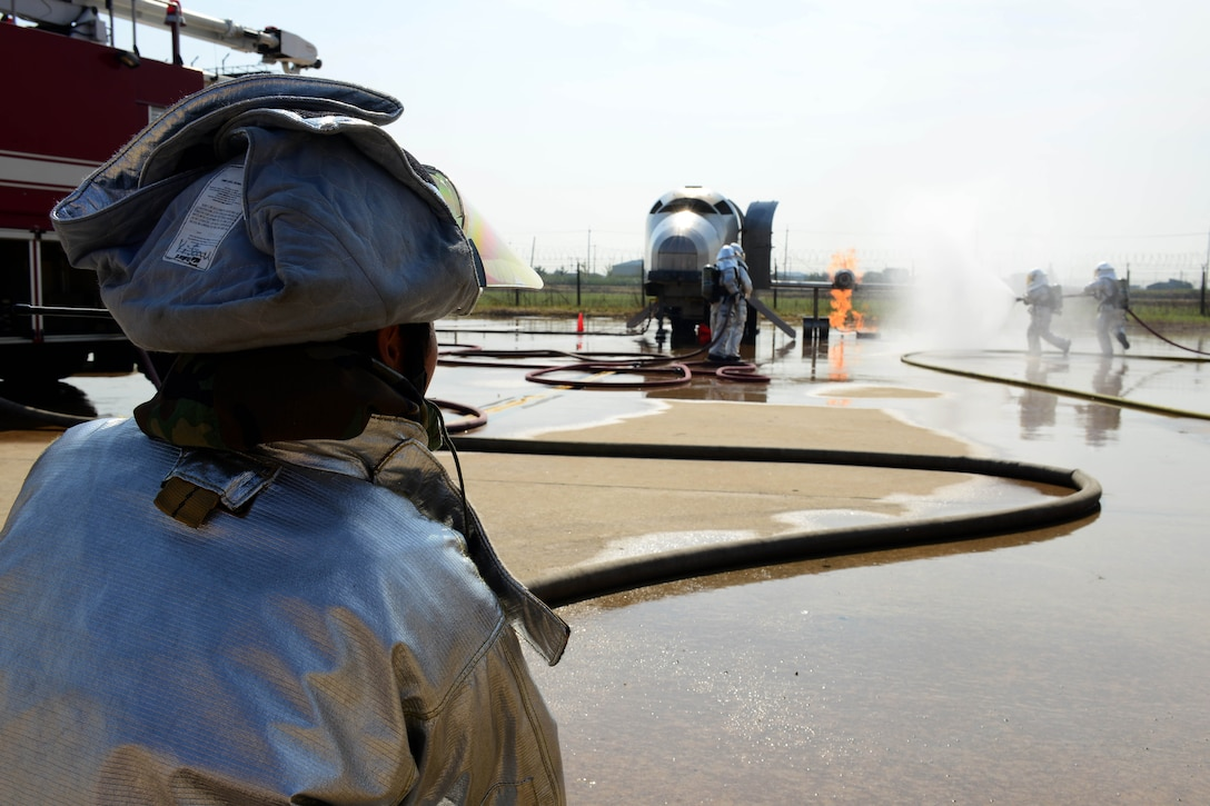 Son U Yi, 8th Civil Engineer Squadron driver operator distances himself away from the fire while helping control the water being provided to extinguish an aircraft fire exercise during Beverly Pack 16-1 at Kunsan Air Base, Republic of Korea, Oct. 07, 2015. The aircraft fire is one of the many exercises that the firefighters participate in as a refresher training to sharpen their skills in the case of a real world emergency. (U.S. Air Force photo by Senior Airman Ashley L. Gardner/Released)