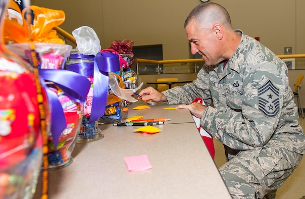 Chief Master Sgt Troy Eden, National Air and Space Intelligence Center command chief, makes his estimates for the candy jar guessing game during the center's annual Combined Federal Capaign kick-off event here, Friday, Oct. 9, 2015. The CFC, established by the federal government in 1961, is the only authorized charitable fundraising campaign for federal employees, both civilian and military. (U.S. Air Force photo by Tech. Sgt. Eunique Thomas)