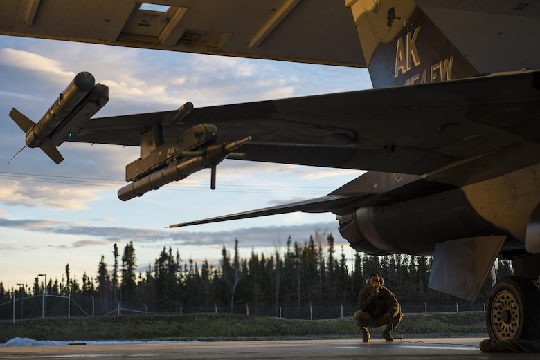Senior Airman Terrence Lawrence, a 354th Aircraft Maintenance Squadron aircraft electrical and environmental systems journeyman, prepares an F-16 Fighting Falcon, assigned to the 18th Aggressor Squadron, for a mission at Eielson Air Force Base, Alaska, Oct. 8, 2015. Lawrence was the first Airman to complete a program called Cut Training, which cross utilizes Airmen to fill undermanned crew chief positions. (U.S. Air Force photo/Staff Sgt. Joshua Turner)