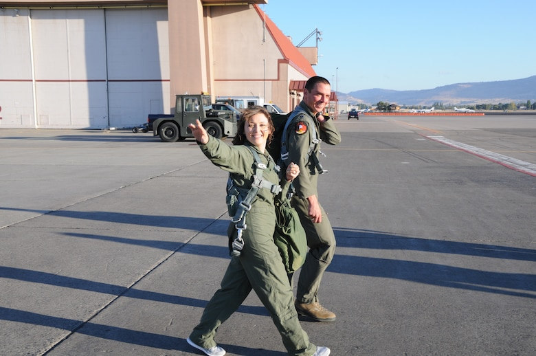 One of the spouses of a 173rd Fighter Wing maintainer waves at her family while stepping to the F-15C with pilot Lt. Col. Jeremy Wieder, 173rd Maintenance Squadron commander,  in preparation for a taxi ride arranged for spouses of maintenance group members, Oct. 4, 2015. During the morning 20 spouses saw first-hand the result of their significant others' work on a day-to-day basis. (U.S. Air National Guard photo by Tech. Sgt. Jefferson Thompson/released)