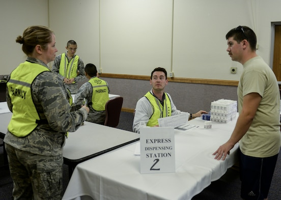 Participants in a public health exercise stand near a point of distribution station at Nellis Air Force Base, Nev., Sept. 30, 2015. The 99th Medical Group conducted a public health exercise on base with local partners in the Clark County area which tested each participant in how they would respond to contracting or deal with individuals who contracted aerosolized tularemia, a serious infection disease which can be used as a biological warfare agent. (U.S. Air Force photo by Airman 1st Class Rachel Loftis)
