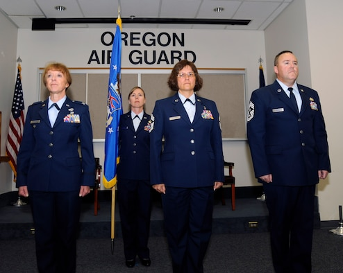 Col. Donna Prigmore, 142nd Fighter Wing Vice Commander, left, outgoing Command Chief Master Sgt. Julie Eddings, center, and incoming 142nd Command Chief Master Sgt. Chris Roper, right, stand at attention during the opening of their Change of Authority ceremony, Sept. 13, 2015, Portland Air National Guard Base, Ore. (U.S. Air National Guard photo by Tech. Sgt. Aaron Perkins, 142nd Fighter Wing Public Affairs/released)