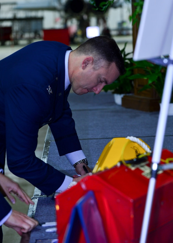 Col. Robert Novotny, 48th Fighter Wing commander, signs a guest book and wheel chock during a memorial ceremony for  Airman 1st Class Darren Phillips, 48th Equipment Maintenance Squadron crew chief, at Royal Air Force Lakenheath, England, Oct. 11, 2015. Phillips died from injuries sustained in a motorcycle accident on Oct. 2. (U.S. Air Force photo by Staff Sgt. Stephanie Longoria/Released)