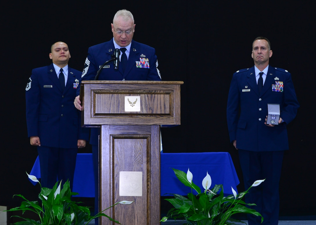 Chief Master Sgt. Timothy Jordan, 48th Equipment Maintenance Squadron superintendent, reads an Air Force Achievement medal citation at a memorial ceremony for Airman 1st Class Darren Phillips, 48th EMS crew chief, for his service and accomplishments while stationed at Royal Air Force Lakenheath, England, Oct. 11, 2015. Phillips died from injuries sustained in a motorcycle accident on Oct. 2. (U.S. Air Force photo by Staff Sgt. Stephanie Longoria/Released)