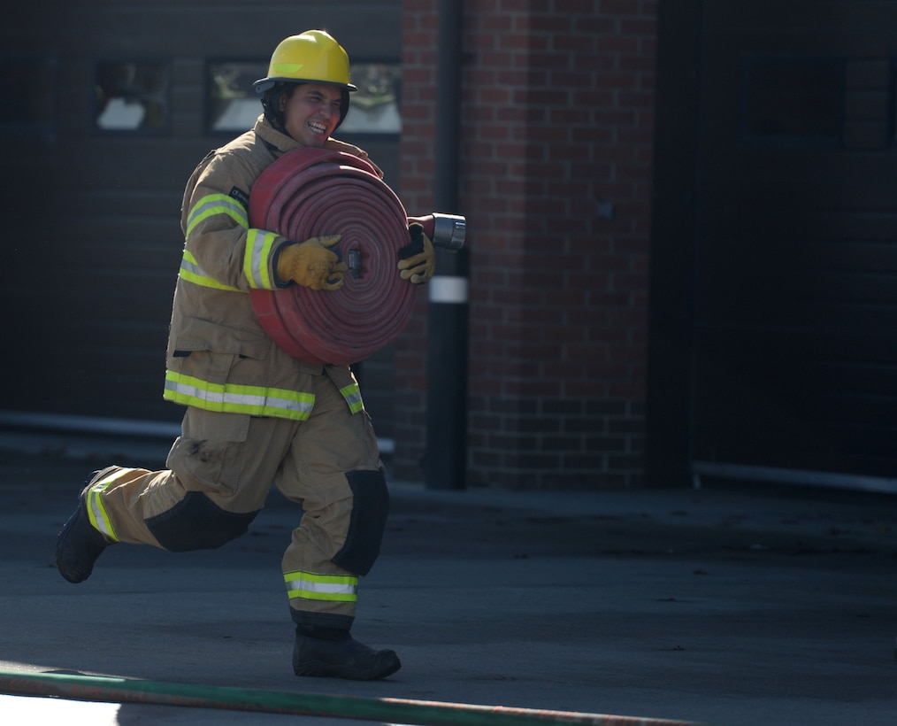 U.S. Air Force Senior Airman Justin Peredo, 100th Civil Engineer Squadron Heating, Ventilation and Air Conditioning journeyman, takes part in the fire muster competition Oct. 8, 2015, on RAF Mildenhall, England. The fire muster enabled families to come together to raise awareness of fire prevention through healthy competition and family friendly activities. (U.S. Air Force photo by Gina Randall/Released)