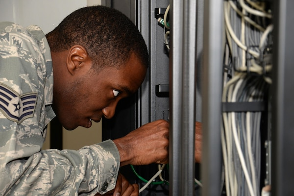 U.S. Air Force Staff Sgt. Christerfer James runs cable on RAF Mildenhall, England, Sept. 4, 2015. James, 100th Communication Squadron Cyber Transport supervisor, was granting RAF Mildenhall users the ability to access the base nonsecure internet protocol router and secure internet protocol router network. (U.S. Air Force photo by Gina Randall/Released)