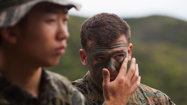 U.S. Marine Corps Cpl. Josh J. Neahusan, right, applies camouflage paint during a sniper training exchange exercise between Marines of the Republic of Korea and the U.S. at Baengnyeongdo, Republic of Korea, Sept. 11, 2015. Marines from both countries exchanged weapon systems, methods of concealment, and capabilities throughout the training. The exercise was part of Korean Marine Exchange Program 15-13, a bilateral training exercise that enhances the ROK and U.S. alliance, promotes stability on the Korean Peninsula, and strengthens ROK and U.S. military capabilities. Neahusan, from Middletown, Maryland, is a scout sniper attached to Echo Company, 2nd Battalion, 3rd Marine Regiment, currently assigned to 4th Marine Regiment, 3rd Marine Division, III Marine Expeditionary Force, under the unit deployment program. The ROK Marines are with 6th Force Recon Company, 6th Brigade, 2nd ROK Marine Corps Division.
