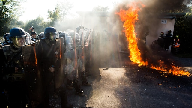 U.S. Marines and French Gendarmerie form a wall of shields as a Molotov cocktail explodes near their feet at the National Gendarmerie Tactical Training Center in Saint-Astier, France, Oct. 9. A platoon of Marines with Special-Purpose Marine Air-Ground Task Force Crisis Response-Africa, had a unique opportunity to train at the center, specialized in restoring order and professional intervention. (