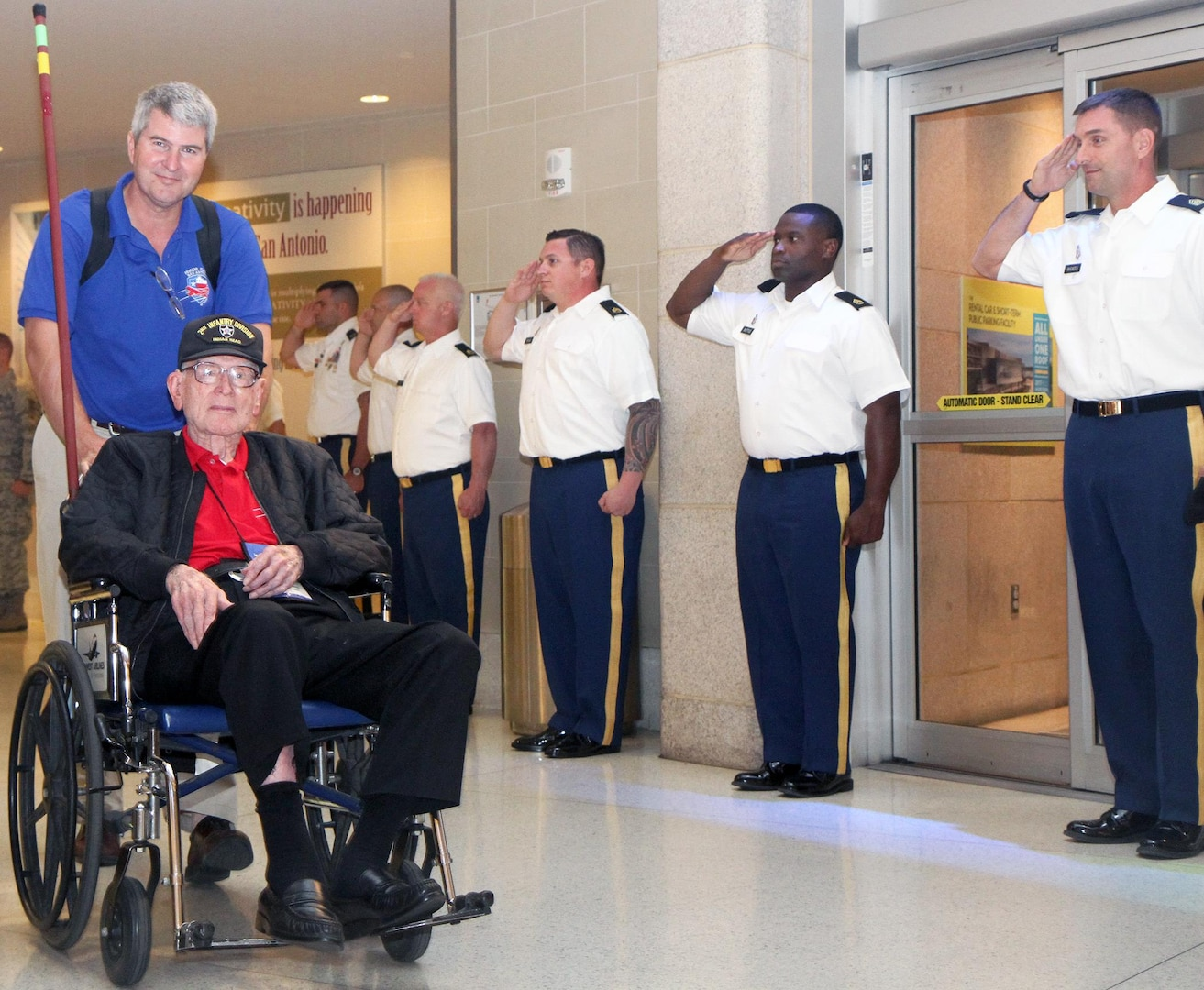 Retired Army Col. Tom Morris is wheeled through the San Antonio International Airport after a late-night return from an honor flight to Washington, D.C. Oct. 3. Morris is a 105-year-old veteran of World War II who fought at Normandy and the Battle of the Bulge.