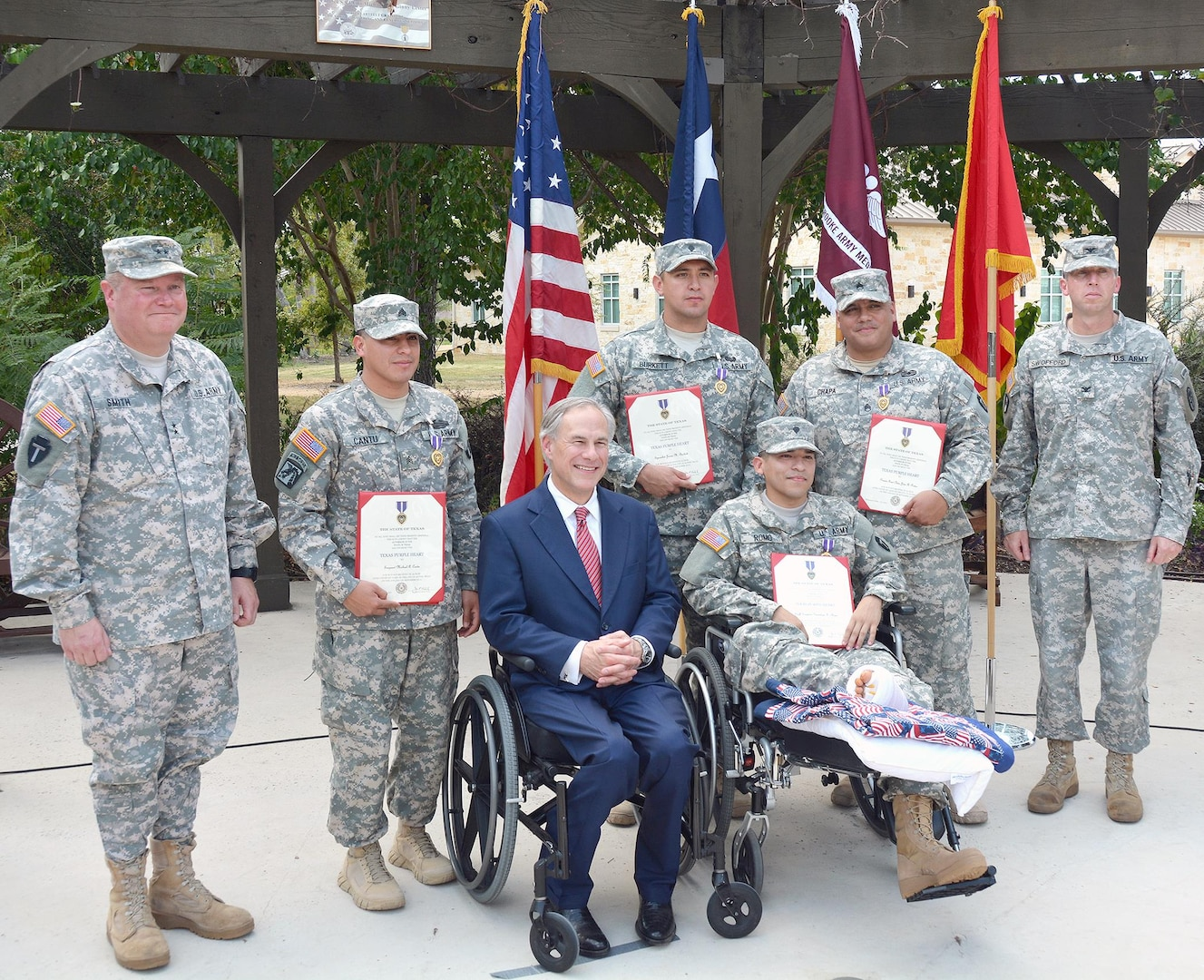 (Standing, from left) Maj. Gen. William L. Smith, Sgt. Michael Cantu, Spc. James Burkett, Staff Sgt. Guadalupe Chapa and Col. Mark Swofford, join Texas Gov. Greg Abbott and Spc. Jose Romo (seated) pose for a photo after the Texas Purple Heart ceremony Sept. 24 at the Warrior and Family Support Center's Purple Heart Garden on Fort Sam Houston. Smith is the Army assistant adjutant general and commander of the Texas Army National Guard and Swofford is the Brooke Army Medical Center deputy commander for administration.