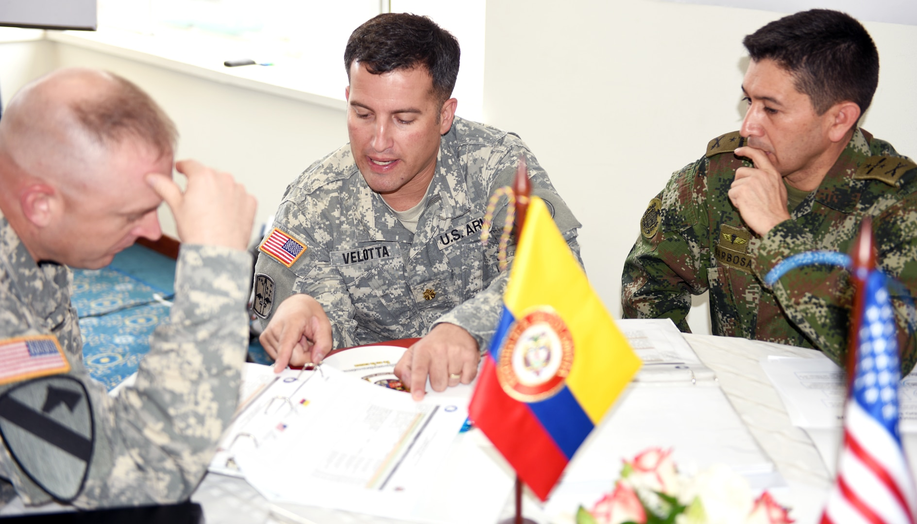 Maj. Bradley Velotta (center), regional affairs directorate translates for Col. Joseph Smith (left),  Headquarters Department of the Army Intelligence (G-2), questions from Col. Carlos Augusto Barbossa (right), Colombian Army Director of Organization Plans and International Relations.