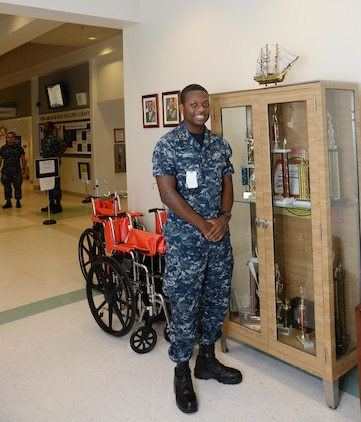 HA Christopher B. Mincey, hospital apprentice, Naval Branch Health Clinic Albany, shares some history and facts as sailors, here, honor the service of the USS Constitution naval ship during a presentation commemorating the Navy's 240th birthday at Marine Corps Logistics Base Albany, Oct. 13. A replica of the historical USS Constitution is displayed atop a trophy case in the lobby area at NBHC Albany.