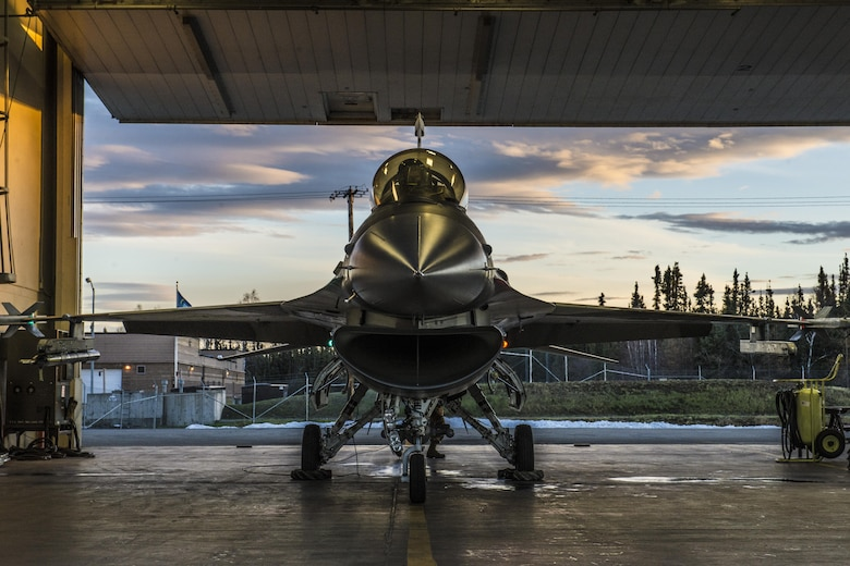 """U.S. Air Force Senior Airman Terrence Lawrence, a 354th Aircraft Maintenance Squadron aircraft electrical and environmental systems journeyman, prepares an F-16 Fighting Falcon assigned to the 18th Aggressor Squadron at Eielson Air Force Base, Alaska, for a mission Oct. 8, 2015. Lawrence was the first Airman to complete a program called """"cut training,"""" which cross utilizes Airmen to fill undermanned crew chief positions. (U.S. Air Force photo by Staff Sgt. Joshua Turner/Released)"""