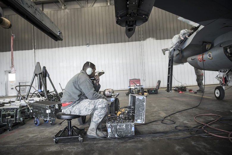 """U.S. Air Force Senior Airman Terrence Lawrence, 354th Aircraft Maintenance Squadron aircraft electrical and environmental systems journeyman, troubleshoots an F-16 Fighting Falcon assigned to the 18th Aggressor Squadron at Eieson Air Force Base, Alaska, Oct. 7, 2015. Lawrence was the first Airman to complete a program called """"cut training,"""" which cross utilizes Airmen to fill undermanned crew chief positions. (U.S. Air Force photo by Staff Sgt. Joshua Turner/Released)"""
