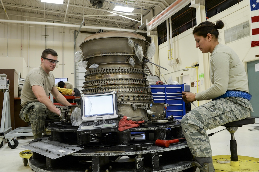 U.S. Air Force Senior Airman Cody Bowman, an aerospace propulsion journeyman, and Staff Sgt. Catalina Cornejo, an aerospace propulsion craftsman, both assigned to the 354th Maintenance Squadron, disassemble an F110-GE-100C jet engine Oct. 8, 2015, during an engine rebuild in the Engine Shop at Eielson Air Force Base, Alaska. Bowman and Cornejo conducted an engine rebuild to find and replace any worn components. (U.S. Air Force photo by Senior Airman Peter Reft/Released)
