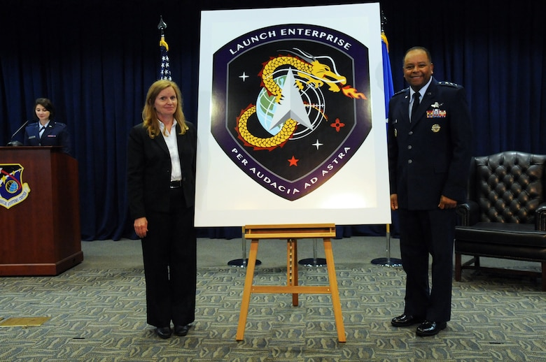 """Lt. Gen. Samuel Greaves, Space and Missile Systems Center commander and Air Force Program Executive Officer for Space and Dr. Claire Leon, the first director of the Launch Systems Enterprise Directorate unveil the new emblem during a brief stand up ceremony, Oct. 14. The Latin phrase, """"Per Audacia Ad Astra"""" translates to """"Through boldness to the stars"""" -- the new motto of the Launch Enterprise Directorate. (U.S. Air Force photo/Van De Ha)"""
