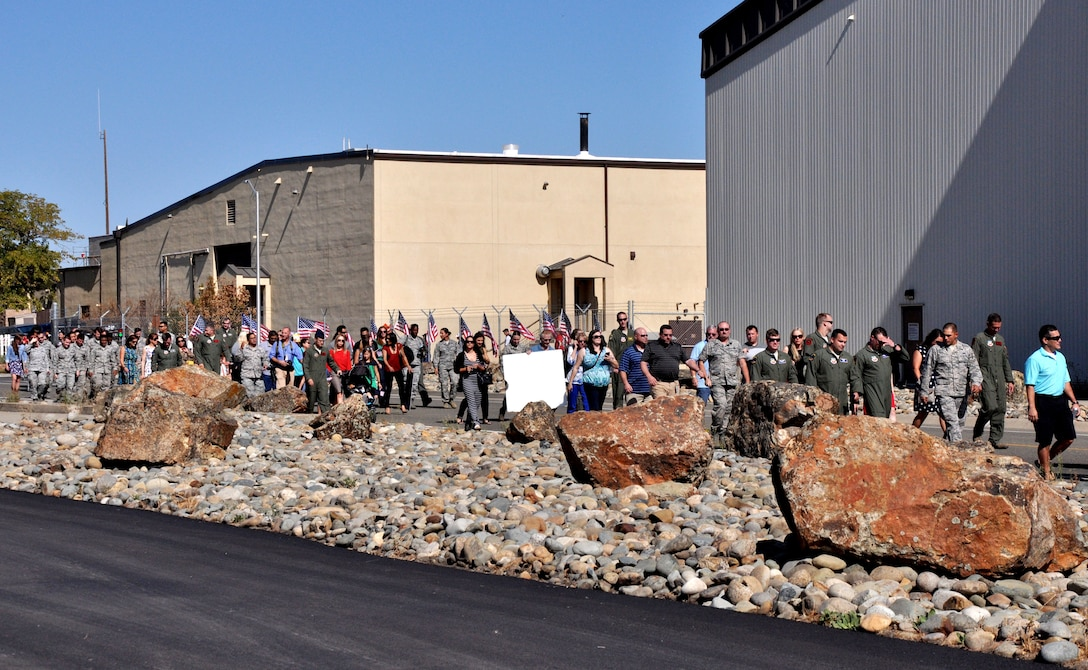 Family, friends and members of Team Beale walk out to the flight line to greet the returning deployed Airmen Oct. 13, 2015, Beale Air Force Base, California. The returning group of Airmen represent the 427th and 306th Reconnaissance Squadrons and completed the final MC-12 deployment from Beale. (U.S. Air Force photo by Staff Sgt. Jeffrey M. Schultze)