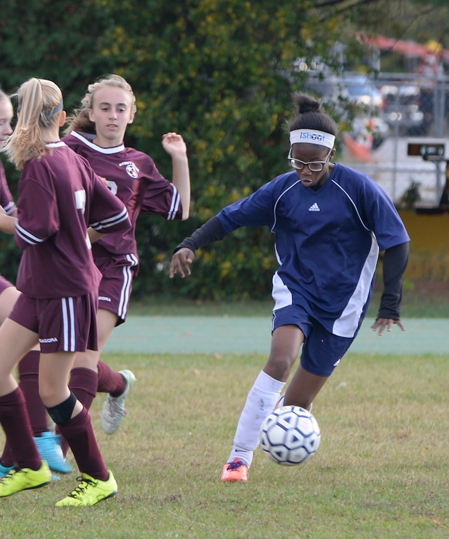 Marcia Green-Williams, right, a member of the Hanscom Middle School Falcons girls' soccer team, dribbles the ball during a home match against the Westford Middle School team at the base track Oct. 14. The Hanscom Middle School team lost the game by a score of 4 to 0. (U.S. Air Force photo by Mark Wyatt)