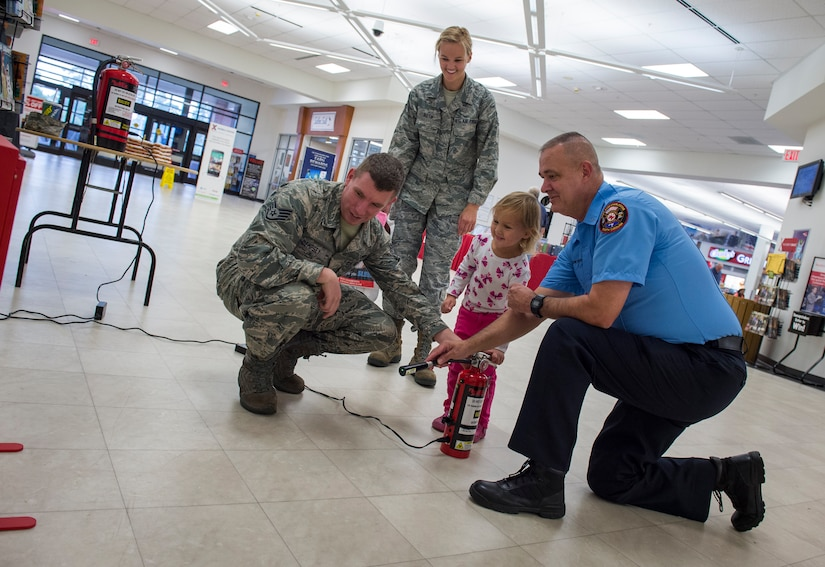 Joint Base Charleston Fire Department firemrn show visitors how to properly put out fires with a fire simulation game during a fire prevention week event Oct. 6, 2015, at the Base Exchange on JB Charleston – Air Base, S.C. Fire prevention week was Oct. 4 through Oct. 10 and the JB Charleston Fire Department hosted several events around the Air Base and Weapons Station. Fire prevention week was established in 1925 by President Calvin Coolidge when close to 15,000 American citizens died in fires the previous year. (U.S. Air Force photo/Airman 1st Class Clayton Cupit)