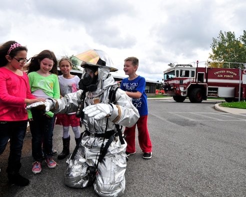 Fire Inspector Joseph Honsberger from the Niagara Falls Air Reserve Station Fire Department shows off a fire reflective suit to a group of children at the Pioneer Village School, Niagara Falls, N.Y. on October 9, 2015. Firefighters from the base were on hand to demonstrate and speak to children about fire safety during the national Fire Prevention Week. (U.S. Air Force photo by Peter Borys)