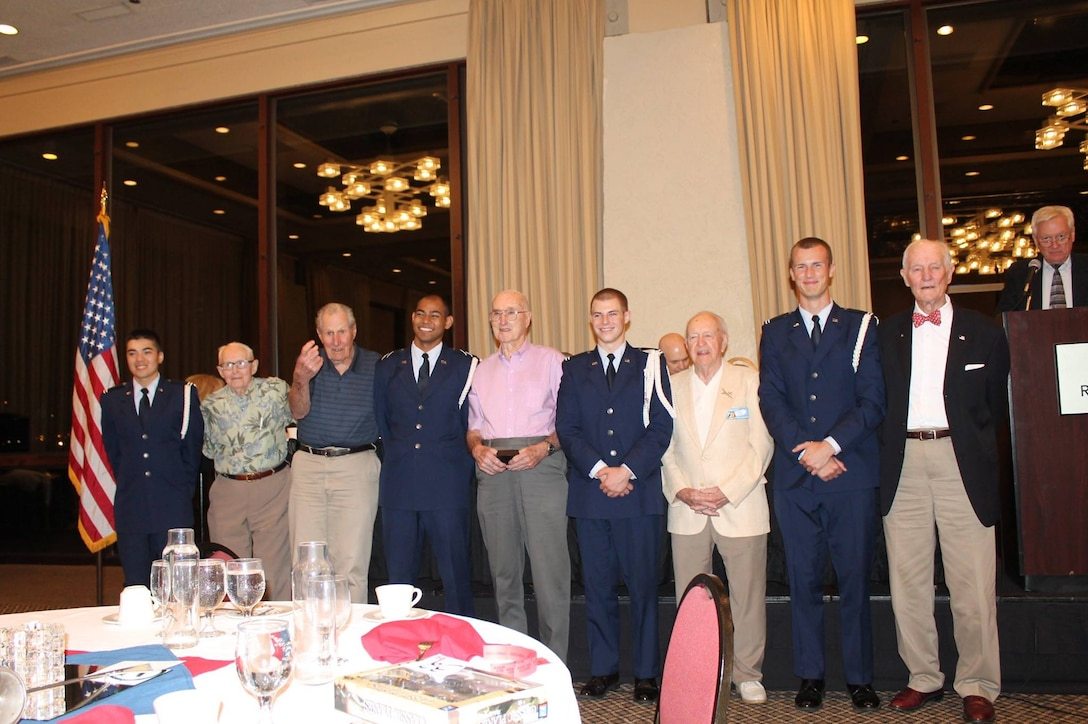 Veterans of the 6th Bomb Group stand with AFROTC cadets from the color guard of the University of Portland's AFROTC Det 695, after the reunion banquet on 12 September 2015 in Portland, Oregon.  From left to right are C/Capt Collin Whitney, Dick Randall, Ed Vincent, C/3C Jacob San Agustin, Virgil Morgan, C/Capt Joseph Baumann, Bob Frick, C/Capt Samuel DeWhitt and Warren Higgins.  The 6th BG Association President, John Creek, Jr., looks on from the podium.  (Courtesy Mr. Philip Conroy)