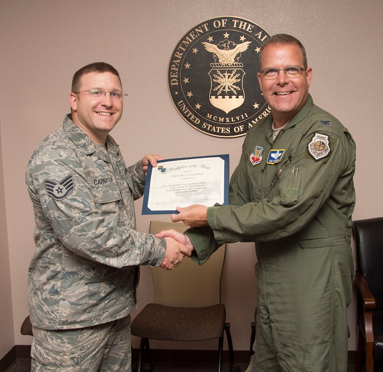 Staff Sgt. Luke Carnathan, 12th Air Force (Air Forces Southern) spectrum manager, smiles after being presented the Warfighter of the Week from Col. Robert Stonemark, 12th AF (AFSOUTH) chief of staff, on Sept. 21, 2015 at Davis-Monthan AFB, Ariz. War Fighter of the Week is an opportunity for the Airmen who represent 12th AF (AFSOUTH) to share their story. The Warfighter of the Week intuitive also aligns with the 12th AF (AFSOUTH) commander's priority of creating a work environment where someone knows you both professionally and personally. (U.S. Air Force photo by Staff Sgt. Adam Grant/Released)
