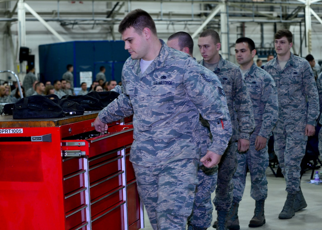 Airmen assigned to the 48th Equipment Maintenance Squadron, placed tools into a toolbox during a memorial ceremony for Airman 1st Class Darren Phillips, 48th EMS crew chief, at Royal Air Force Lakenheath, England, Oct. 11, 2015. Phillips' toolbox was locked for the last time, allowing his team to say a final goodbye. He died from injuries sustained in a motorcycle accident on Oct. 2. (U.S. Air Force photo by Staff Sgt. Stephanie Longoria/Released)