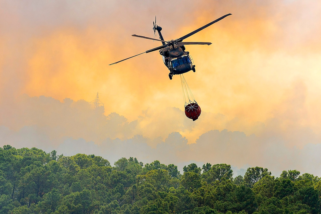 A Texas Army National Guard UH-60 Black Hawk helps fight wildfires threatening homes and property near Bastrop, Texas, Oct. 14, 2015. U.S. Army National Guard photo by Sgt. 1st Class Malcolm McClendon