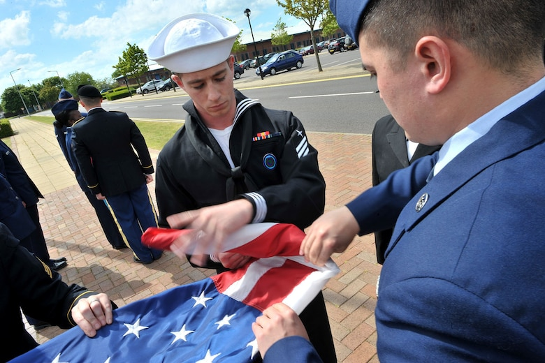 U.S. Navy Reserve Seaman Sheridan, center, U.S. Africa Command analyst and RAF Molesworth Joint Honor Guard member, assists other members with folding the American flag during a retreat ceremony at RAF Molesworth, United Kingdom, June 5, 2015. Retreat ceremonies are a part of the various events the newly-reconstructed honor guard team performs. (The last names of personnel have been romoved for security purposes) (U.S. Air Force photo by Staff Sgt. Ashley Hawkins/Released)
