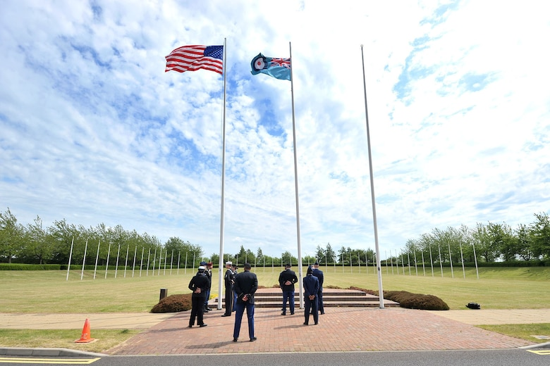 U.S. Service members with the RAF Molesworth Joint Honor Guard stand at parade rest before lowering the American and RAF Ensign flags, during a retreat ceremony at RAF Molesworth, United Kingdom, June 5, 2015. The newly-reconstructed honor guard team consists of U.S. Army, Marine Corps, Navy and Air Force personnel who showcase the American flag throughout England and other countries, such as Germany. (U.S. Air Force photo by Staff Sgt. Ashley Hawkins/Released)