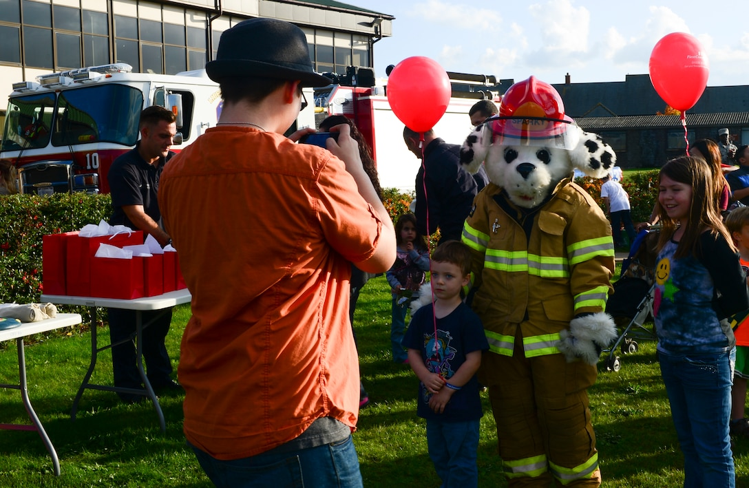 Children greet Sparky the Firedog at Royal Air Force Lakenheath, England, Oct. 9, 2015 as part of National Fire Prevention Week festivities. Liberty Airmen and their families were taught fire safety, received a tour of the fire truck and were able to try on fireman gear. (U.S. Air Force photo by Senior Airman Dawn M. Weber/Released)