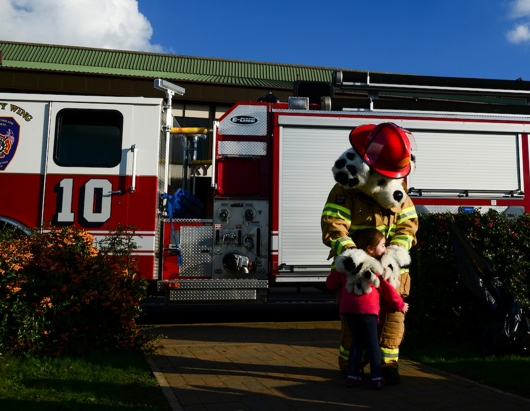 A child hugs Sparky the Firedog at Royal Air Force Lakenheath, England, Oct. 9, 2015, as part of National Fire Prevention Week. Liberty Airmen and their families attended to learn about fire safety, toured a fire truck and try on fireman gear. (U.S. Air Force photo by Senior Airman Dawn M. Weber/Released)