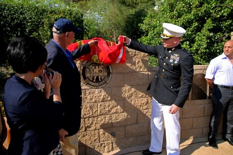 Lieutenant Col. Edward W. Powers, commanding officer of Marine Light Attack Helicopter Squadron 469, 3rd Marine Aircraft Wing, unveils the HMLA 469 memorial during Park Semper Fi's 10th anniversary ceremony at San Clemente, Calif., Oct. 11, 2015. The ceremony paid tribute to Marines with HMLA 469 who gave their lives during a humanitarian mission in Nepal, May 12, 2015.