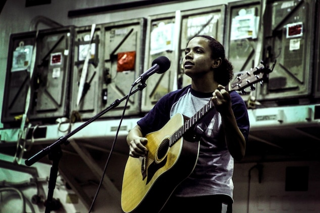 GULF OF ADEN (July 12, 2015) U.S. Marine Lance Cpl. Brianna Mikus sings and plays her guitar during a talent show in the hangar bay of the amphibious assault ship USS Essex (LHD 2). Mikus is a radio operator with Combat Logistics Battalion 15, 15th Marine Expeditionary Unit. The Essex finds time to enhance unit moral by highlighting Marines and Sailors with the 15th MEU and Essex Amphibious Ready Group's talents during their deployment. The 15th MEU is embarked on the Essex ARG and deployed to maintain regional security in the U.S. 5th Fleet area of operations. (U.S. Marine Corps photo by Cpl. Elize McKelvey/Released)