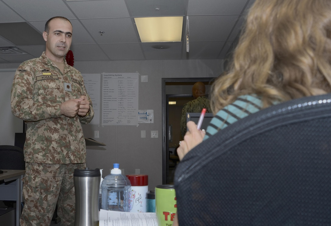 """Pakistan Army Maj. Qaisar Khan, a student in the Basic Public Affairs Specialist Course at the Defense Information School on Fort Meade, Md., talks with Katie Walsh, his journalism instructor, on Oct. 5, 2015. Kahn went to Walsh for advice on the use of """"Miss,"""" """"Ms."""" and """"Mrs."""" in formal introductions in the United States."""